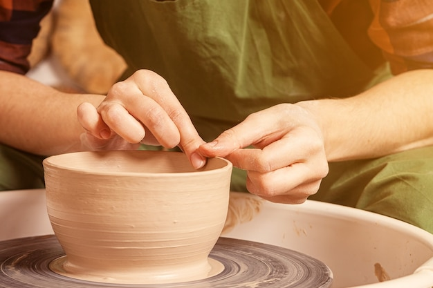 Крупным планом женщина-гончар в клетчатой рубашке и зеленом фартуке красиво лепит глубокую чашу из коричневой глины.