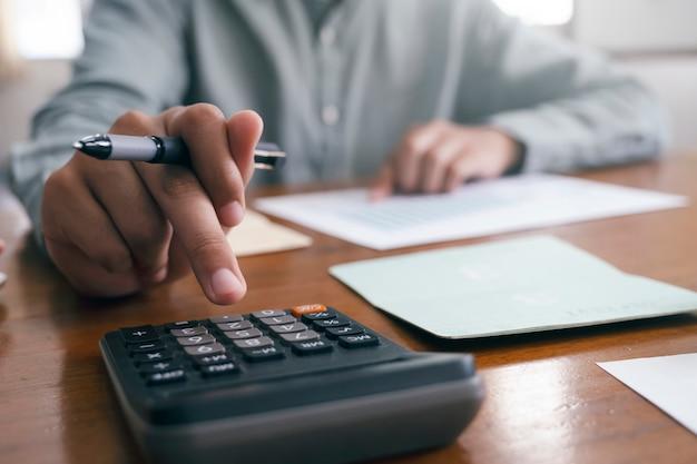 Крупным планом бухгалтер с помощью калькулятора.