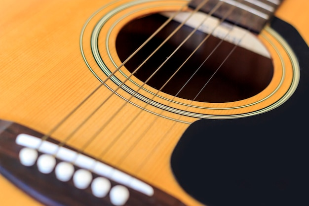 Closeup acoustic guitar with soft-focus and over light in the background