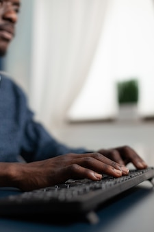 Closeup of african american hands typing management strategy on keyboard working at business presentation using university platform during lockdown in living room. computer user at home