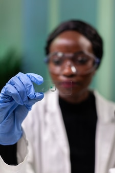 Closeup of african american microbiologist woman looking at green leaf sample working at medical experiment in microbiology hospital laboratory. botanist doctor analyzing genetically modified plants