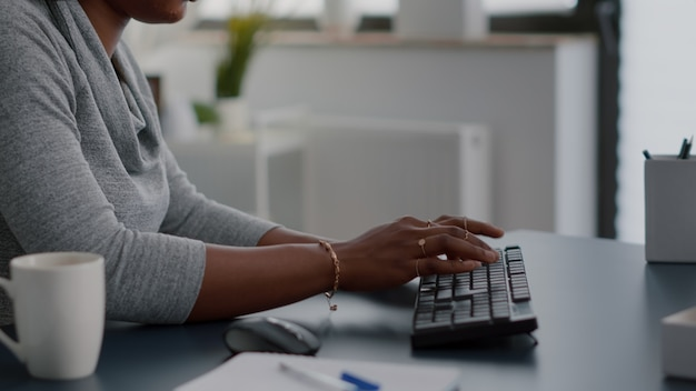 Closeup of african american student hands typing information for communication project