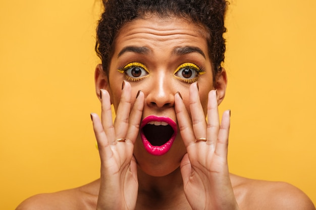 Closeup african american woman emotionally shouting or calling on camera putting hands at mouth isolated, over yellow wall