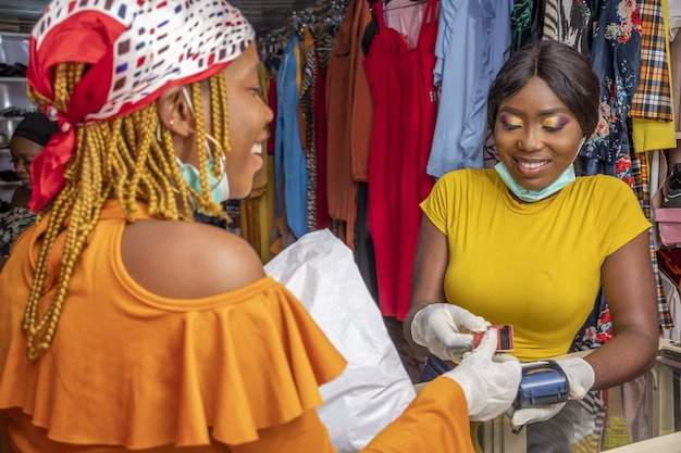 Closeup of an african female with latex gloves and a facemask paying with a credit card at a shop