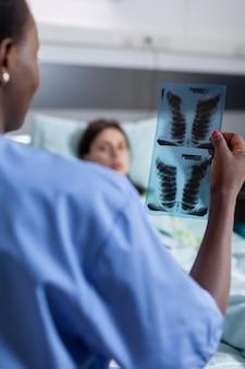 Primo piano dell'infermiera afroamericana che analizza i raggi x dei polmoni che controllano il paziente della donna malata di guarigione del guaritore