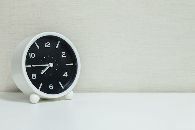 Closeup alarm clock for decorate in a quarter to eight on wood desk