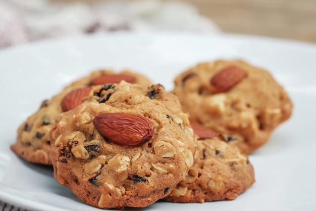 クローズアップアーモンドクッキーまたは健康的なスナックは、ぼやけた背景の白いプレートに積み重ねられます。
