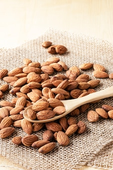 Closeup almonds nut are poured from wooden spoon on sack and table.