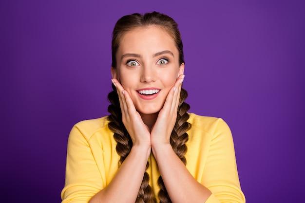Крупным планом удивительная дама с длинными косами, держащая руки на скулах, слушайте хорошие новости, скидки, финальный период носить повседневный желтый джемпер, изолированный фиолетовый цвет стены