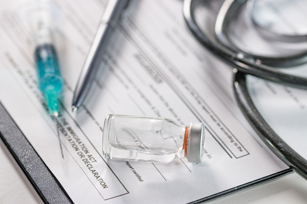 Closeup of an ampoule and a needle syringe on a document with a phonendoscope