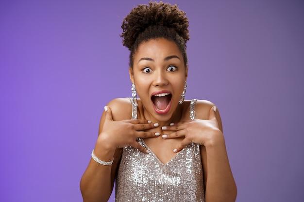 Удивленная крупным планом шокированная шикарная гламурная афроамериканка получила идеальный сюрприз, указывая на ...