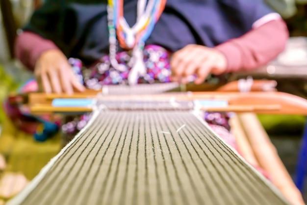 ぼやけたタイアーヒル族の老婦人のクローズアップと作物生地が織り上げています