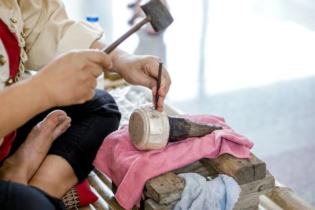 Крупный план и урожай руки тайландца демонстрируют резную серебряную чашу для воды в чиангмае, таиланд.