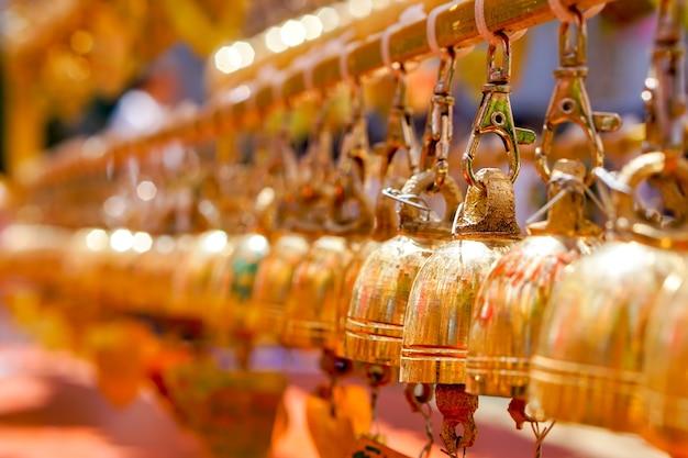 Группа взглядов крупного плана и перспективы в составе малых золотых колоколов висят в тайском виске на расплывчатой предпосылке.