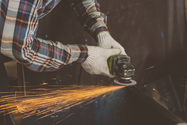 Closeup angle grinder hand holding and grinding the spare parts of metal
