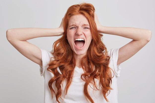 Primo piano della giovane donna stupita arrabbiata con capelli rossi ondulati lunghi