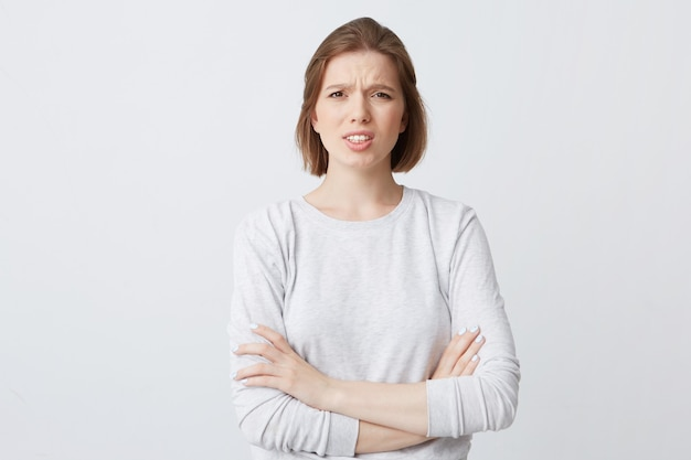Closeup of angry annoyed young woman in longsleeve standing with arms crossed