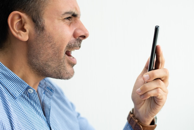 Closeup of angry business man shouting at smartphone