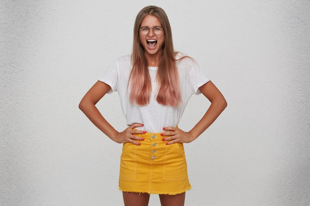 Closeup of angry crazy young woman wears t shirt, yellow skirt and spectacles keeps hands on waist and shouting isolated over white wall