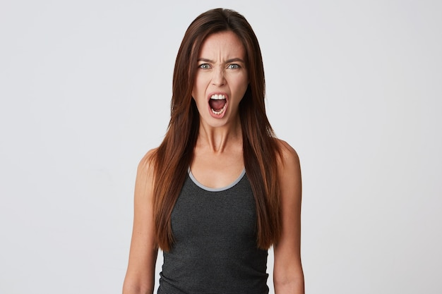 Closeup of angry mad young woman with long hair and opened mouth feels irritated and screaming