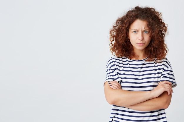 Il primo piano della giovane donna riccia sollecitata arrabbiata indossa la maglietta a strisce ha problemi