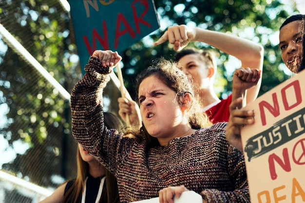 Closeup of angry teen girl protesting demonstration holding posters antiwar justice peace