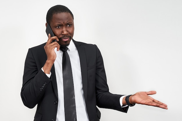 Closeup of angry young african man screaming while talking on smartphone