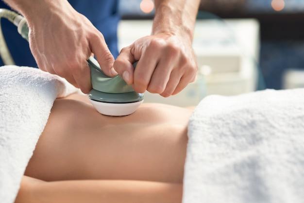 Closeup of anticellulite apparatus massage of female belly