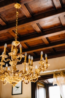 Closeup of an antique gold chandelier in the interior of an old villa