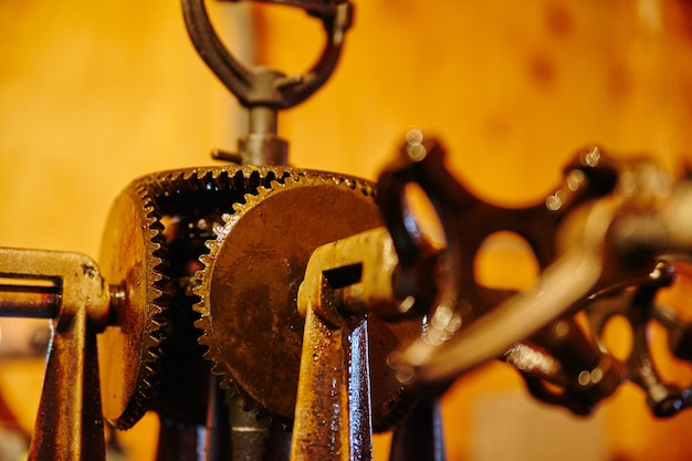 Closeup of an antique machine with orange lighting with gears and handles