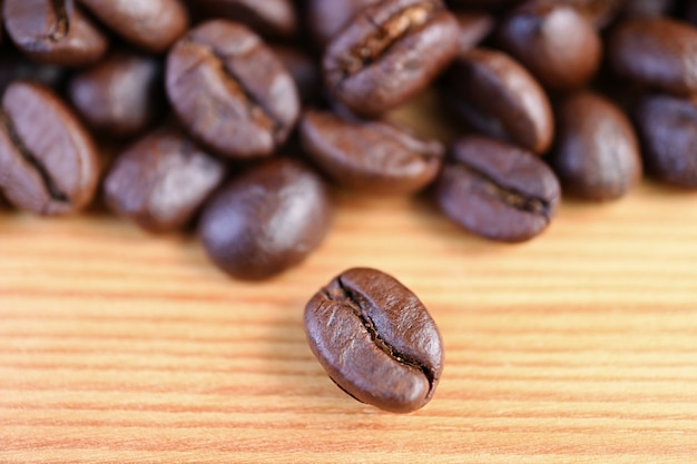 Closeup an arabica roasted coffee bean with blurry coffee beans pile in the backdrop