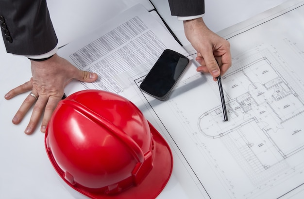 Closeup of architect hands revising a house project plans