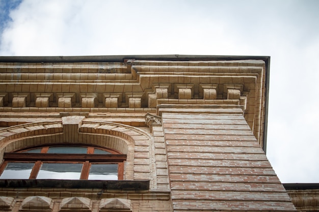 Closeup of architectural details and window of an old building against the blue sky