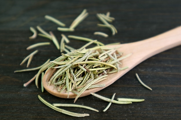 Closeup aromatic dried rosemary in a wooden spoon