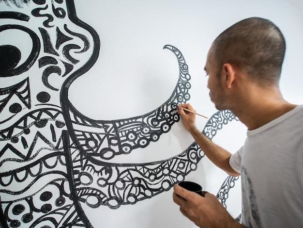白いセメントの壁にタコの形の抽象的なパターンを描くクローズアップアーティスト。