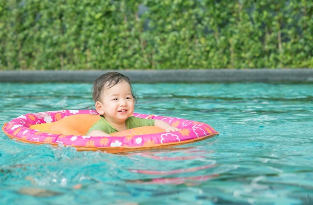 Closeup asian boy sit in a boat for children in the swimming pool