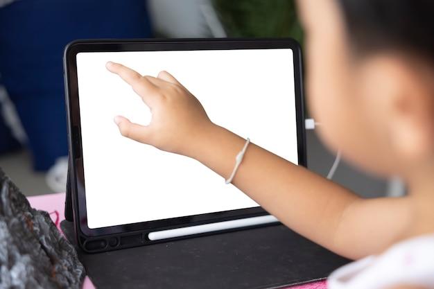 オンラインeラーニングシステムを介して勉強しているクローズアップアジアの少年ビデオ通話の遠方のクラスを持っている