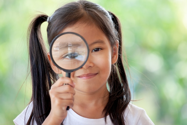 Closeup of asian child girl looking through a magnifying glass