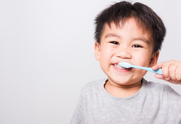 Closeup asian face, little children boy hand holds toothbrush he brushing teeth myself