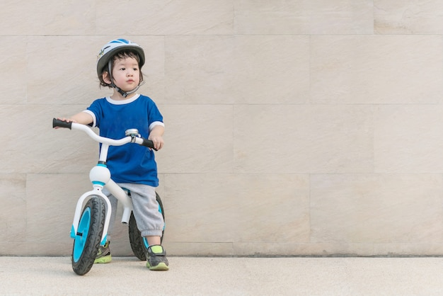 Closeup asian kid ride a bicycle and look at space of picture