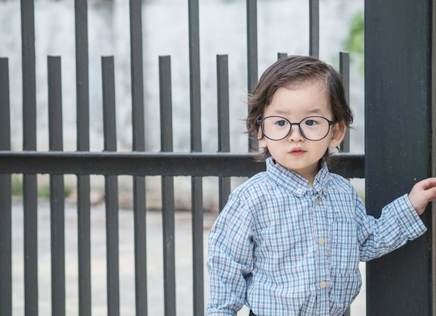 Closeup asian kid with eyeglasses stand in front of steel fence textured background