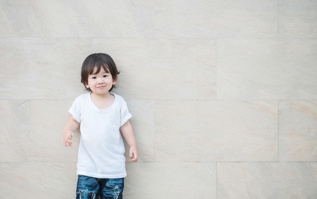 Closeup asian kid with smile face on marble wall
