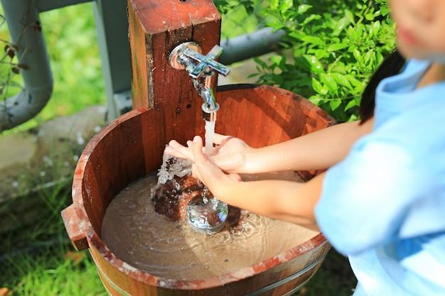 水シンクで手を洗うクローズアップアジアの小さな子供の女の子