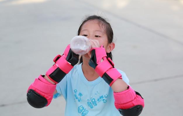 クローズ アップ アジアの小さな女の子の子供は、ボトルから水を飲む安全と保護具を着用します。