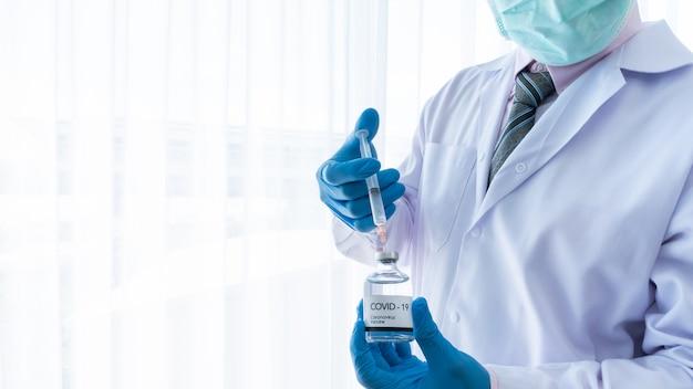 근접 촬영 아시아 남자 의사 covid-19 또는 코로나 바이러스 백신의 유리 병에 얼굴 마스크와 채우기 주사기를 착용
