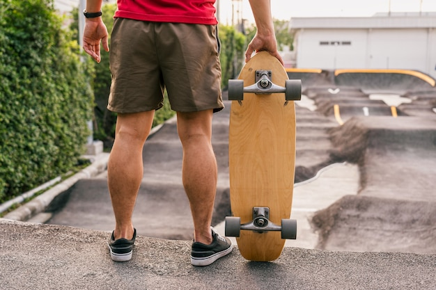 Азиатский мужчина крупным планом, держащий серфинг или скейтборд в скейт-парке pumptrack
