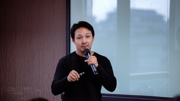 Closeup asian speaker or lecture with casual suit on the stage in front of the room presen