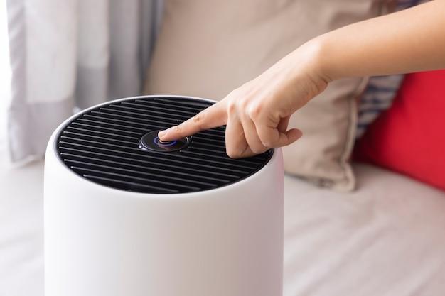근접 촬영 아시아 여성이 침실에서 공기 청정기 기계의 버튼을 눌러 pm 25를 보호합니다.
