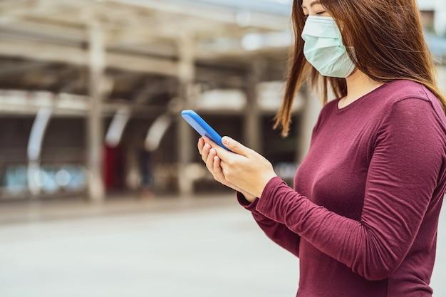 安全医療フェイスマスクとスマート携帯電話を使用してクローズアップアジアの女性の手