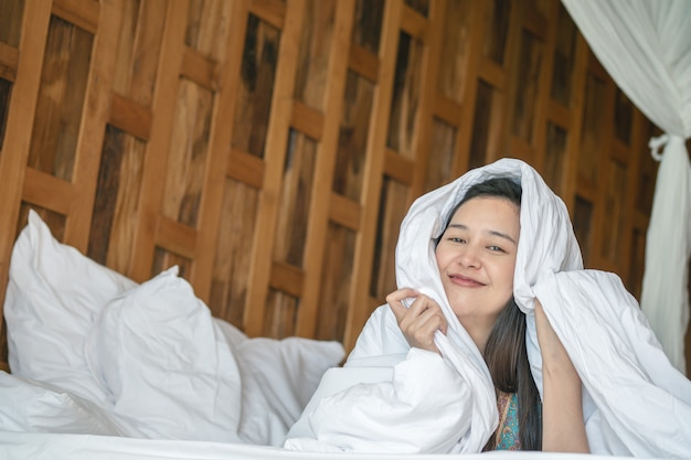 Closeup asian woman lie on bed under blanket with smile face in the morning